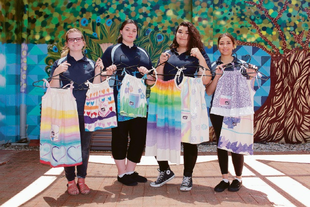 St Clare's students sewing to Dress a Girl Around the World