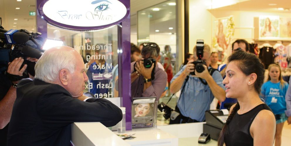 Former PM John Howard - seen here with Brow Shape store owner Sarika Gevaria - hit the campaign trail on Friday.