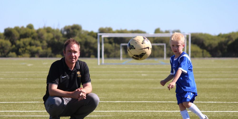 Brad Hassell watches his son Archie (6) practice taking a penalty kick.