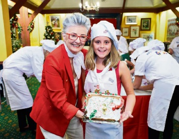 464098pa Hannah Rasmussen (10), of Kallaroo, gets a helping hand from Maud Edmiston (Miss Maud) in creating her gingerbread house. Picture: Jeff Atkinson