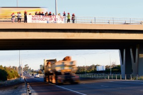 Residents hang the banner over the Thomas Road bridge over the Kwinana Freeway during morning peak hour.