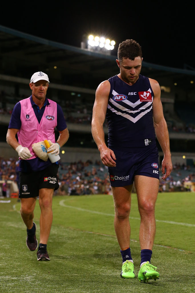 Hayden Ballantyne walks to the change rooms with the team physio after injuring his hamstring during the JLT Community Series AFL match against Carlton last Friday. Picture: Paul Kane/Getty Images