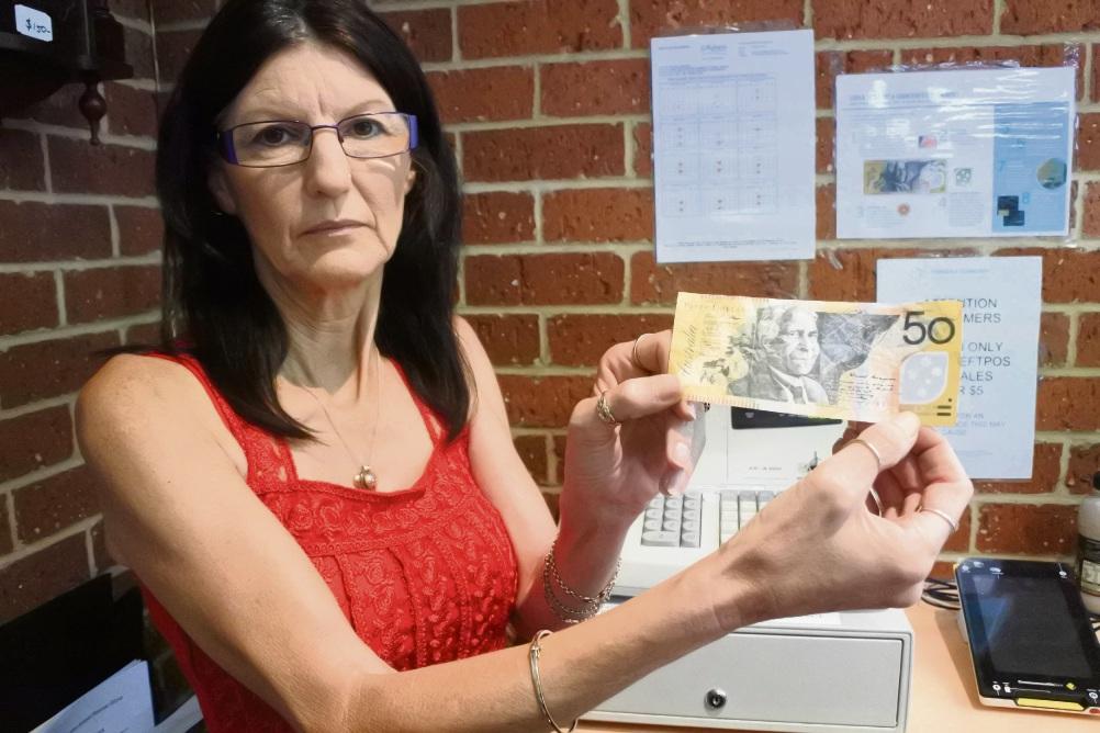 Animal Welfare Op-Shop Rockingham supervisor Trish Pendlebury with the fake $50 she discovered.