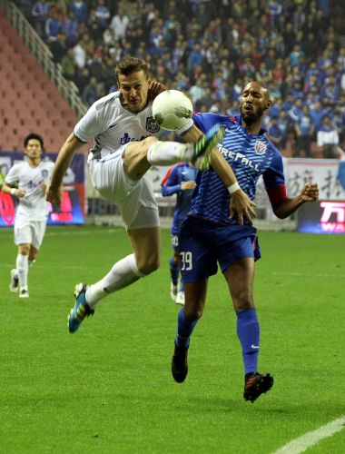 Lucian Goian during his time with Tianjin Teda in the Chinese Super League battling against Shanghai Shenhua's Nicolas Anelka. Picture: VCG/VCG via Getty Images