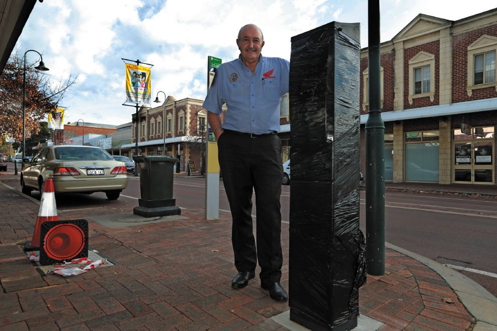 Local business owner Eddie Peters with one of the covered parking meters. Picture: Martin Kennealey        www.communitypix.com.au   d438922