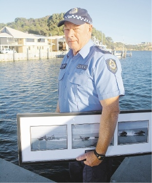 Retiring Senior Sergeant Greg Trew with a framed present from Shoreline Marine Fabrication of new patrol boats.
