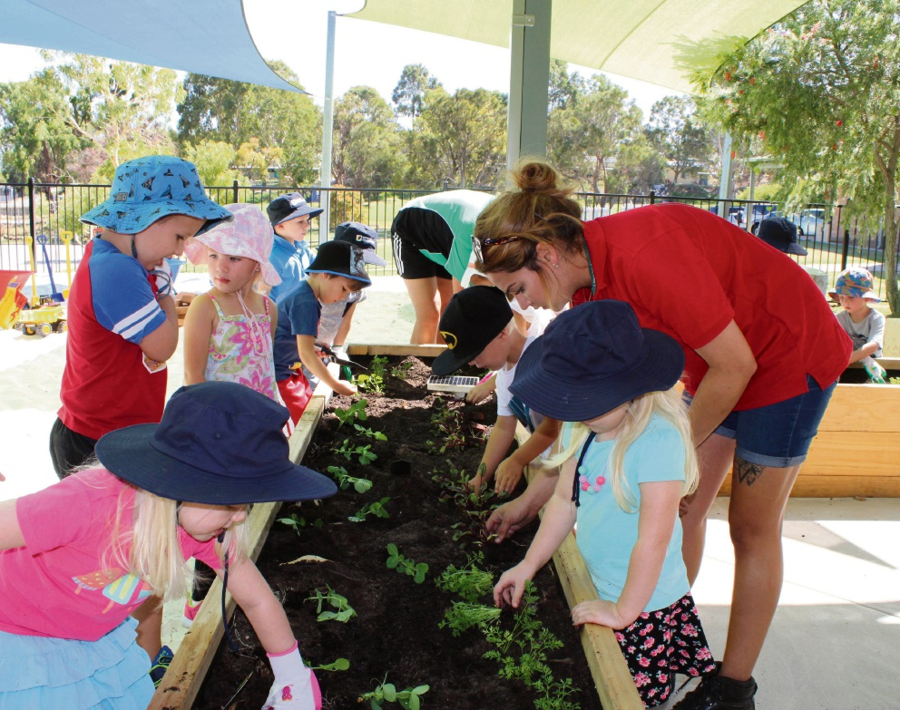 Bunnings staff help students plant a vegetable garden.