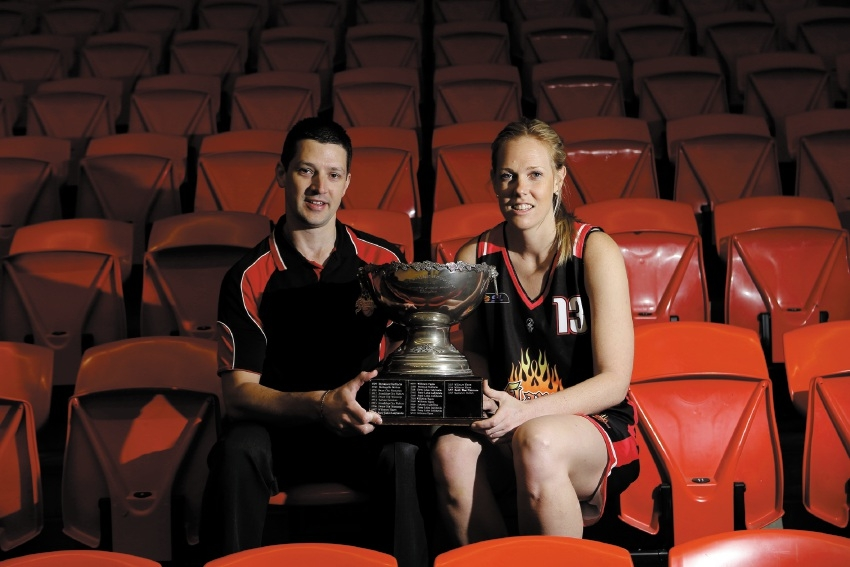 Ryan Petrik, here with Rockingham Flames player Kaye Tucker, coached the Flames to the 2014 trophy.        d425318