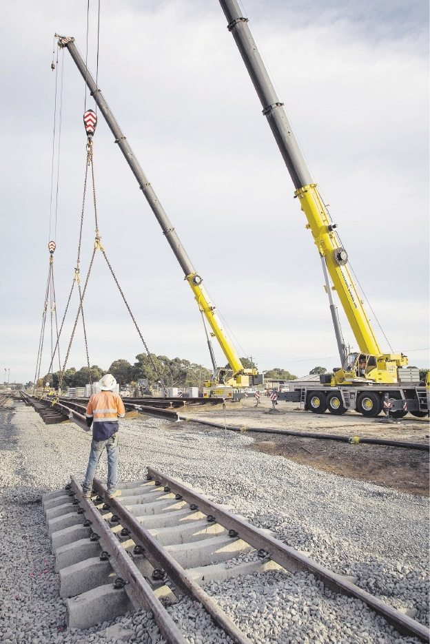 A worker cuts the old rail line in preparation for the new rail bridge line.A giant crane lifts a new section of rail line into position.Pictures: Jacaranda Photography