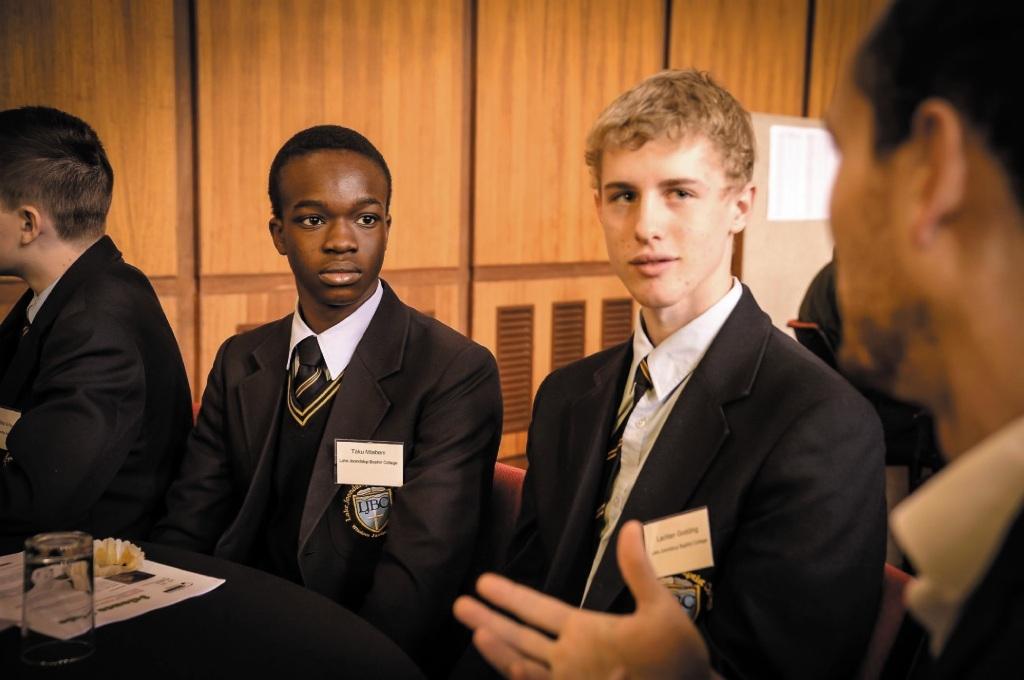 Lake Joondalup Baptist College students Taku Mtabeni and Lachlan Godding speak to Chevron Australia petroleum engineer Michael Cullingford