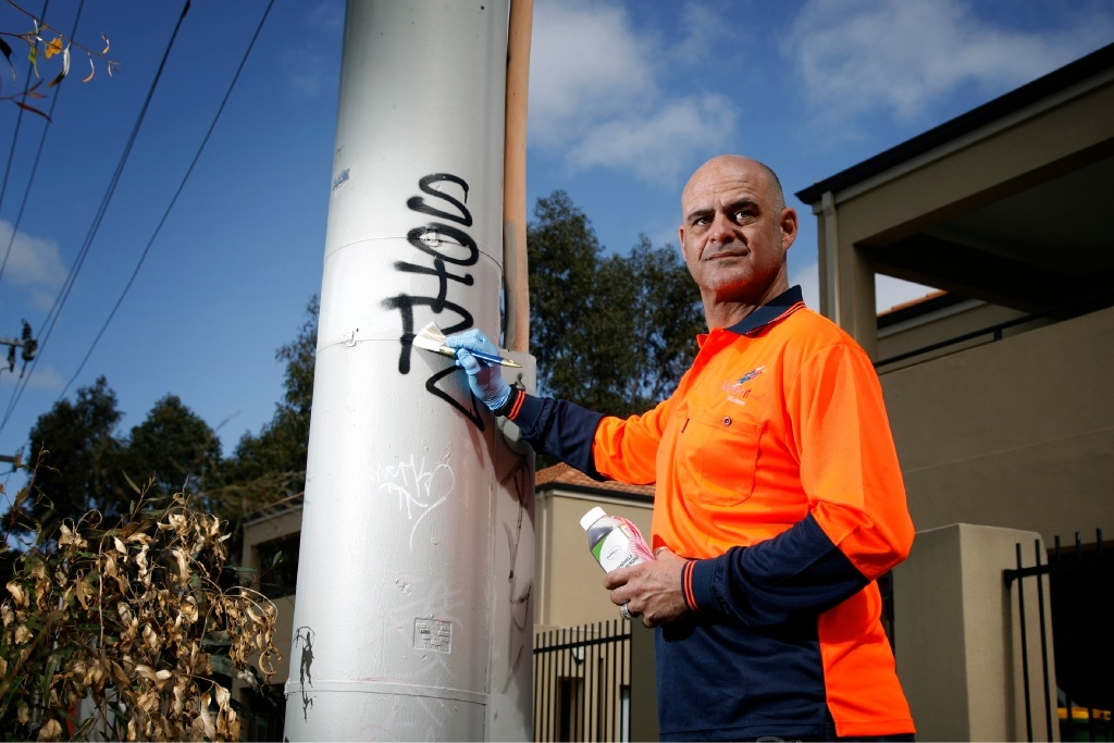 Paul Brent  gets rid of graffiti sprayed on to an electrical pole in Maddington. Picture: Marie Nirme www.communitypix.com.au   d443565