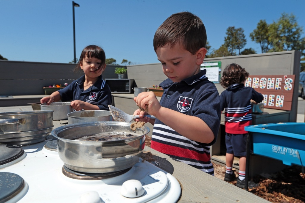 Kindergarten students Eliana Chang, Arlie Carbone and Arjun Sanger learn the finer points of mud cookery. Picture: Martin Kennealey        www.communitypix.com.au   d444190