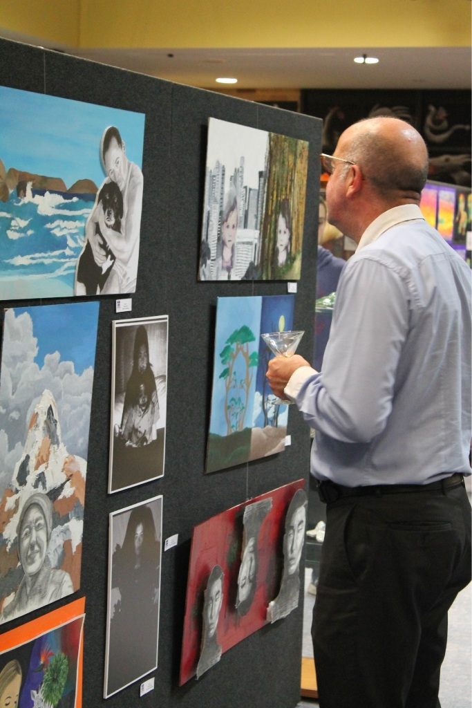 Stephen Meagher having a closer look at the Year 11 mixed media portraits.