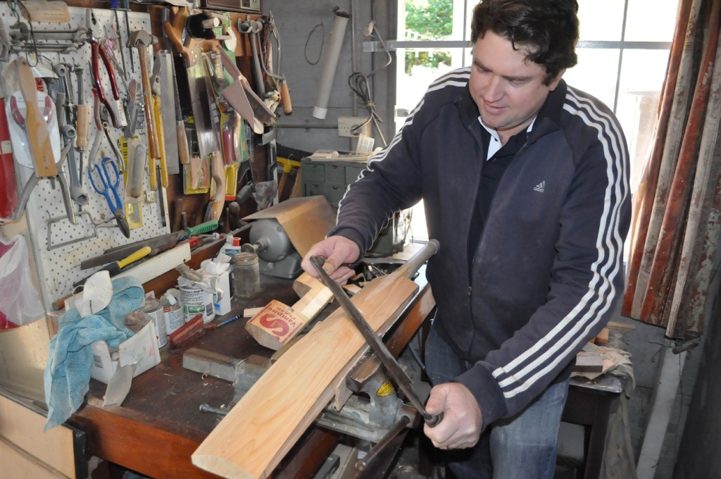 Toby Richardson uses a drawknife to take a lot of wood off quickly during the bat-shaping process.