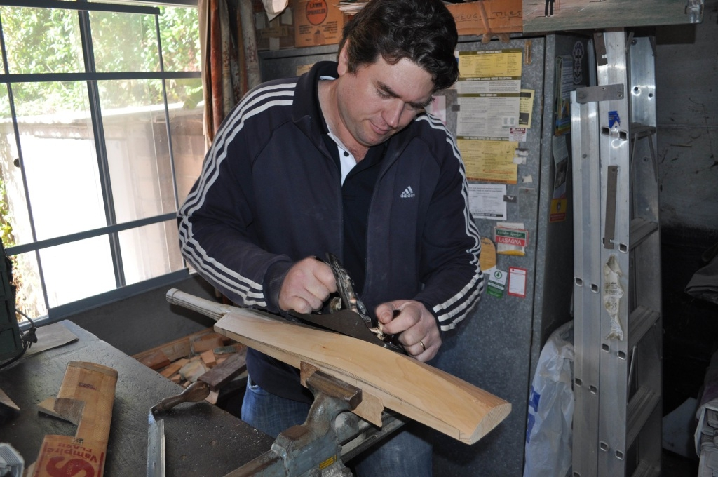 Toby Richardson shaping a cleft of willow into a new cricket bat.