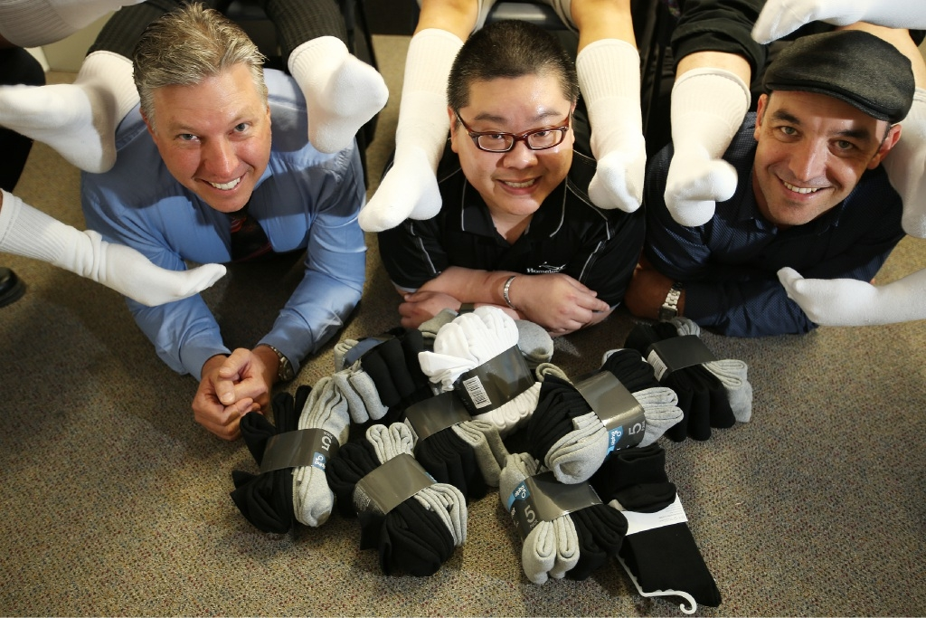 Wayne Smith, of City Toyota, podiatrist Aloysius Ong and James Corby, of Oracle Digital Marketing, help promote Socks in the City for Homeless Healthcare. Picture: Andrew Ritchie                                                                                                                d444118