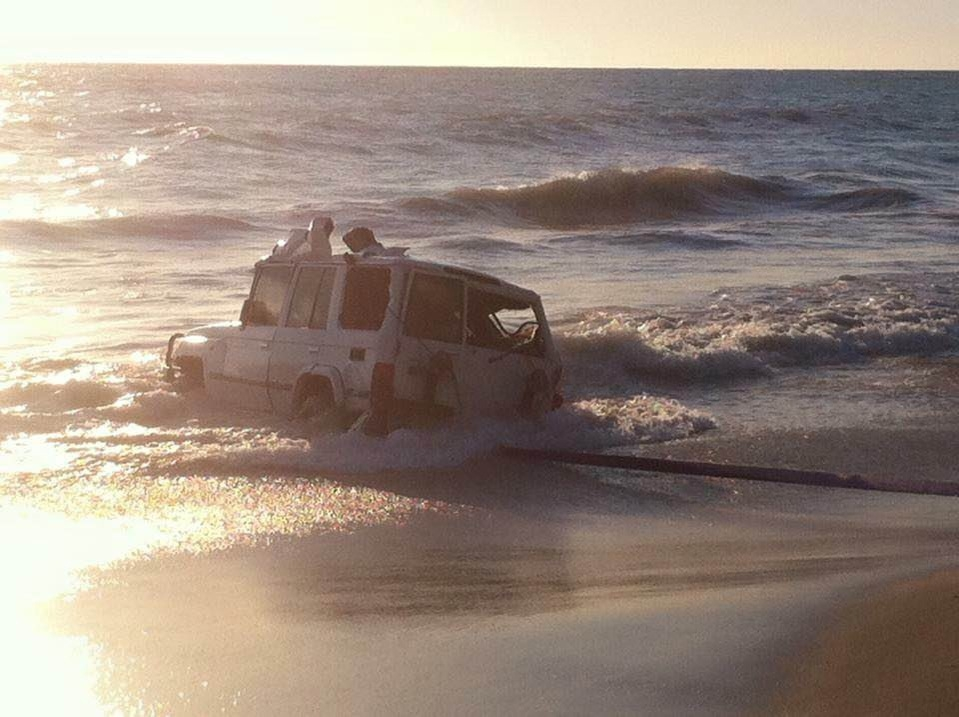 A tow truck retrieves the four-wheel-drive from the ocean, near Wilbinga, on Tuesday. Picture courtesy |McCallum Towing