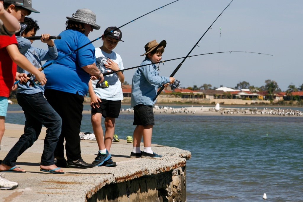 Andrew Russell-Brown (far right) has a go at fishing.Picture: Marie Nirme        www.communitypix.com.au   d444857
