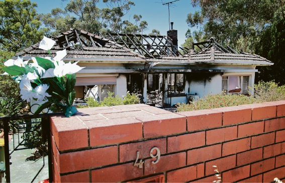 Picture of the floral tribute and damaged house. Picture: David Baylis