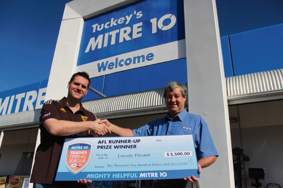Lincoln Flindell receives his footy tipping prize from Tuckey's Hardware Pinjarra owner John Tuckey.