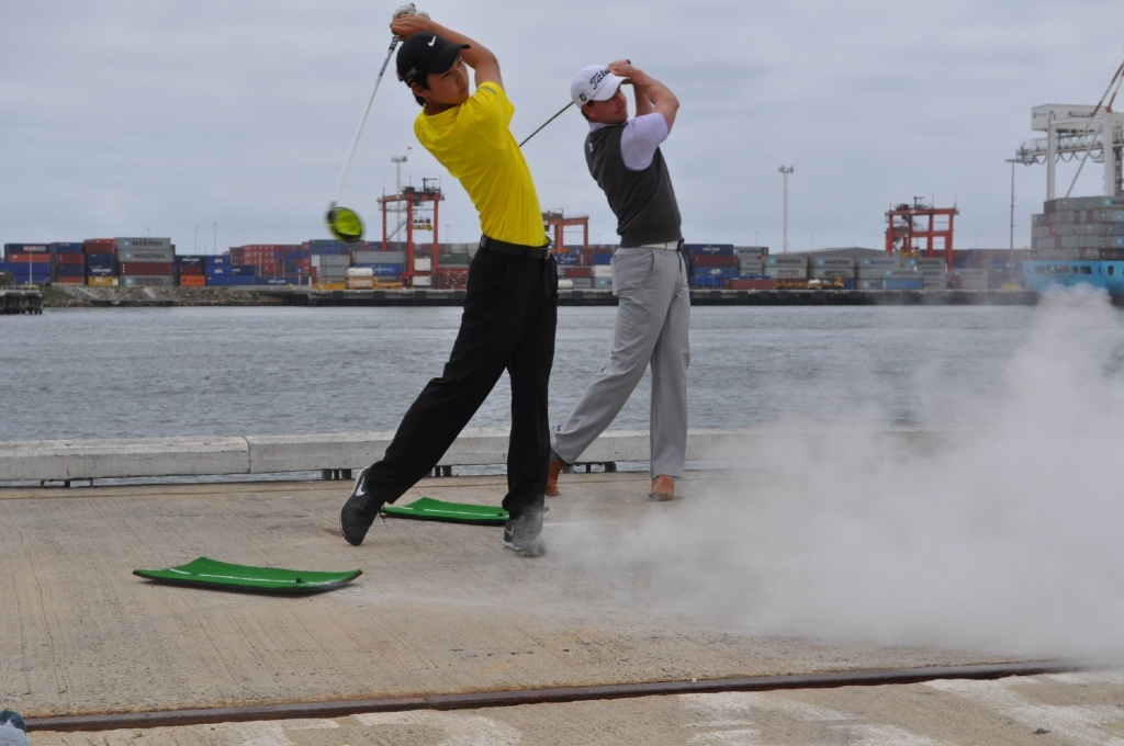Min Woo Lee (front) and Brett Rumford practise their swing with exploding golf balls.