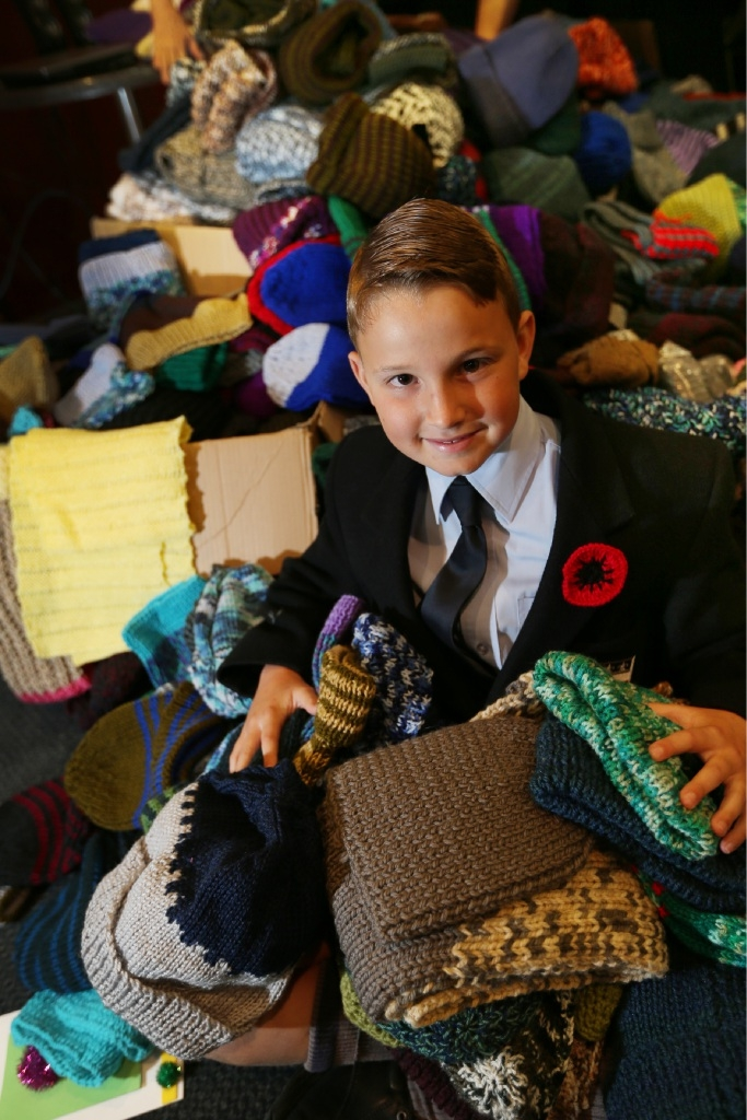 Guildford Grammar student William Cutler (9), of Mt Lawley, with some of the knitted scarves and beanies for Diggers stationed overseas. Picture: Andrew Ritchie        www.communitypix.com.au   d446168