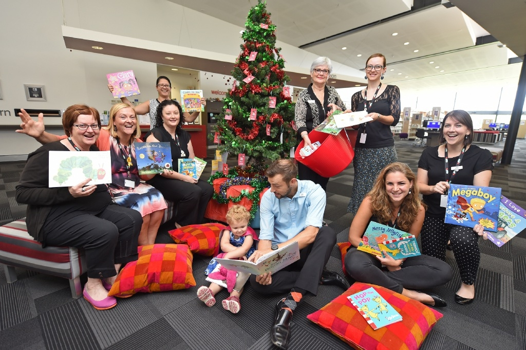 Librarian Hamish Dixon reads to Charlotte Ambrose (2), surrounded by South Perth library staff and Mayor Sue Doherty.Picture: Jon Hewson           d446459