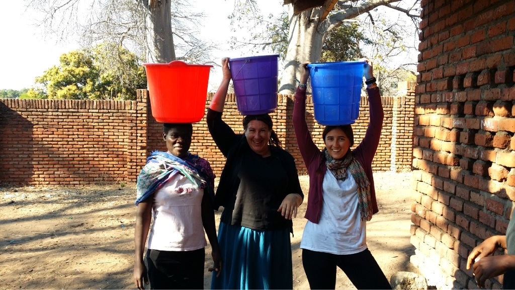 orphanage teacher Edith Kasinja, Ardross resident Nola Formentin and Spanish volunteer Laura Nestares practice balancing buckets on their head at Monkey Bay, in Malawi.