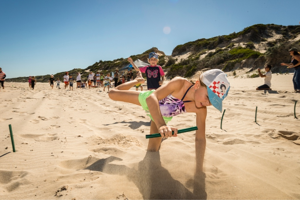 Tia Nimmo diving into the sand, followed by Lily Nimmo, at previous beach events in Eglinton.