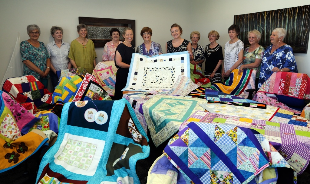Sara Browne and Kara Cheah from Ngala receive  the gift of quilts from Coralie Clarke and the other Crafty Girls. Picture: Martin Kennealey        d447074