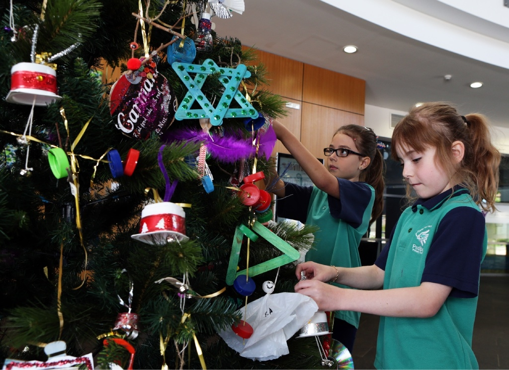 Year 2 students Sayge Arkley and Sascha Muir decorate a tree with their recycled creations. Picture: Martin Kennealey        www.communitypix.com.au   d446724