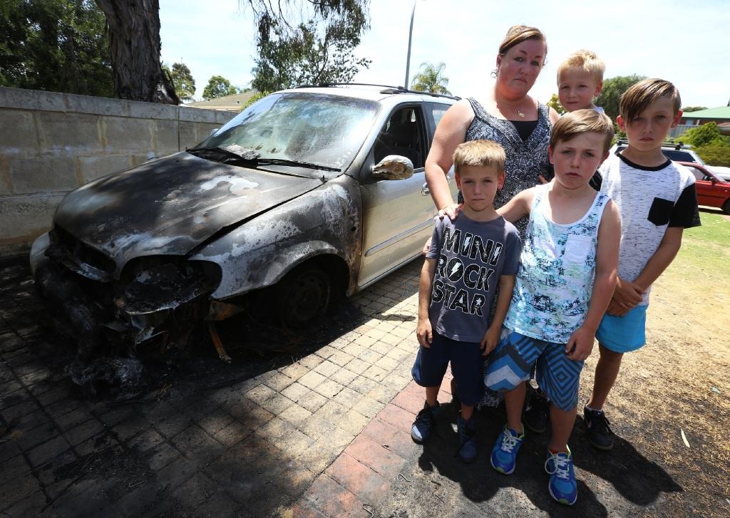 Jodie Salmon with children Ashton (6), Cooper (7), Travis (3) and Seth (10) and her burnt-out car. Picture: Matt Jelonek           d447332