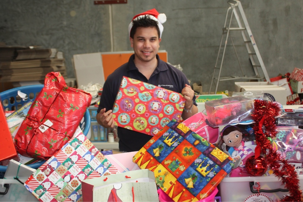 Volunteer Keenan Klassen puts Christmas hampers together.