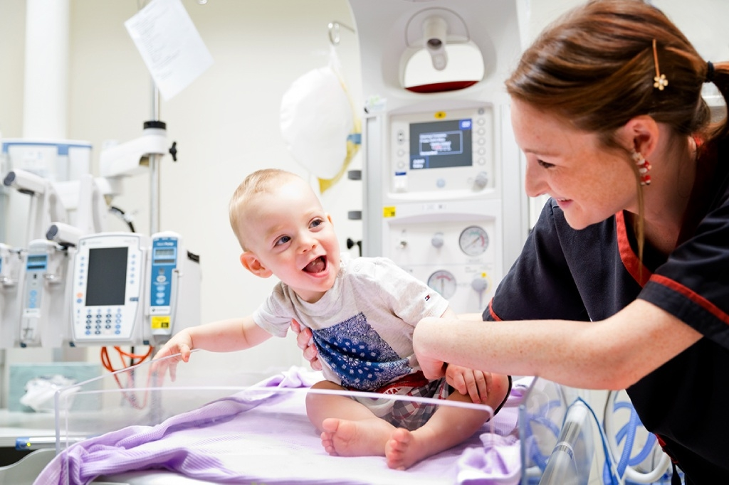 Fiona Stanley Hospital clinical nurse Alice Eames got a big smile from baby Luca Rapp when he returned to help |celebrate the first anniversary of the maternity and |neonatal units.