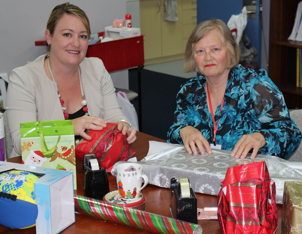 Emily Hamilton and Glen Banks wrap gifts for the UnitingCare Christmas Appeal.