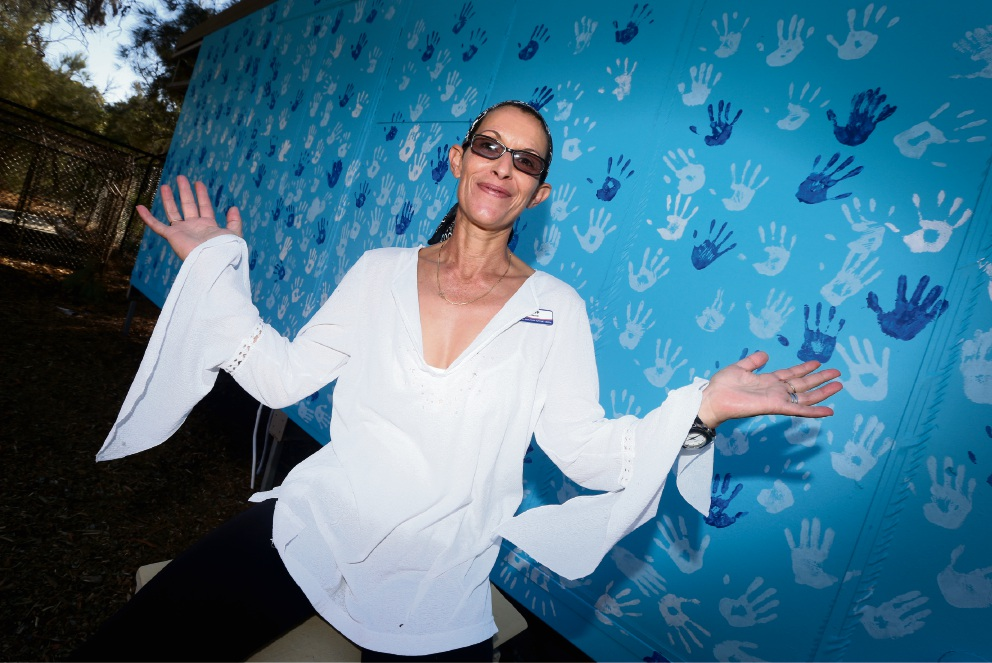 Leeming SHS Education Support Centre teacher Louisa Franceschini-Piil in front of the wall the school decorated with handprints in support of World Autism Awareness Day.
