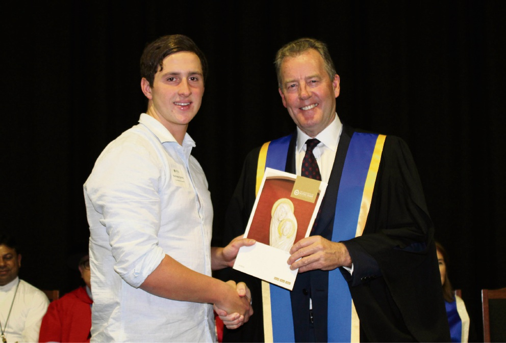Nicholas Elphick accepts his scholarship from Chancellor Peter Prendiville.