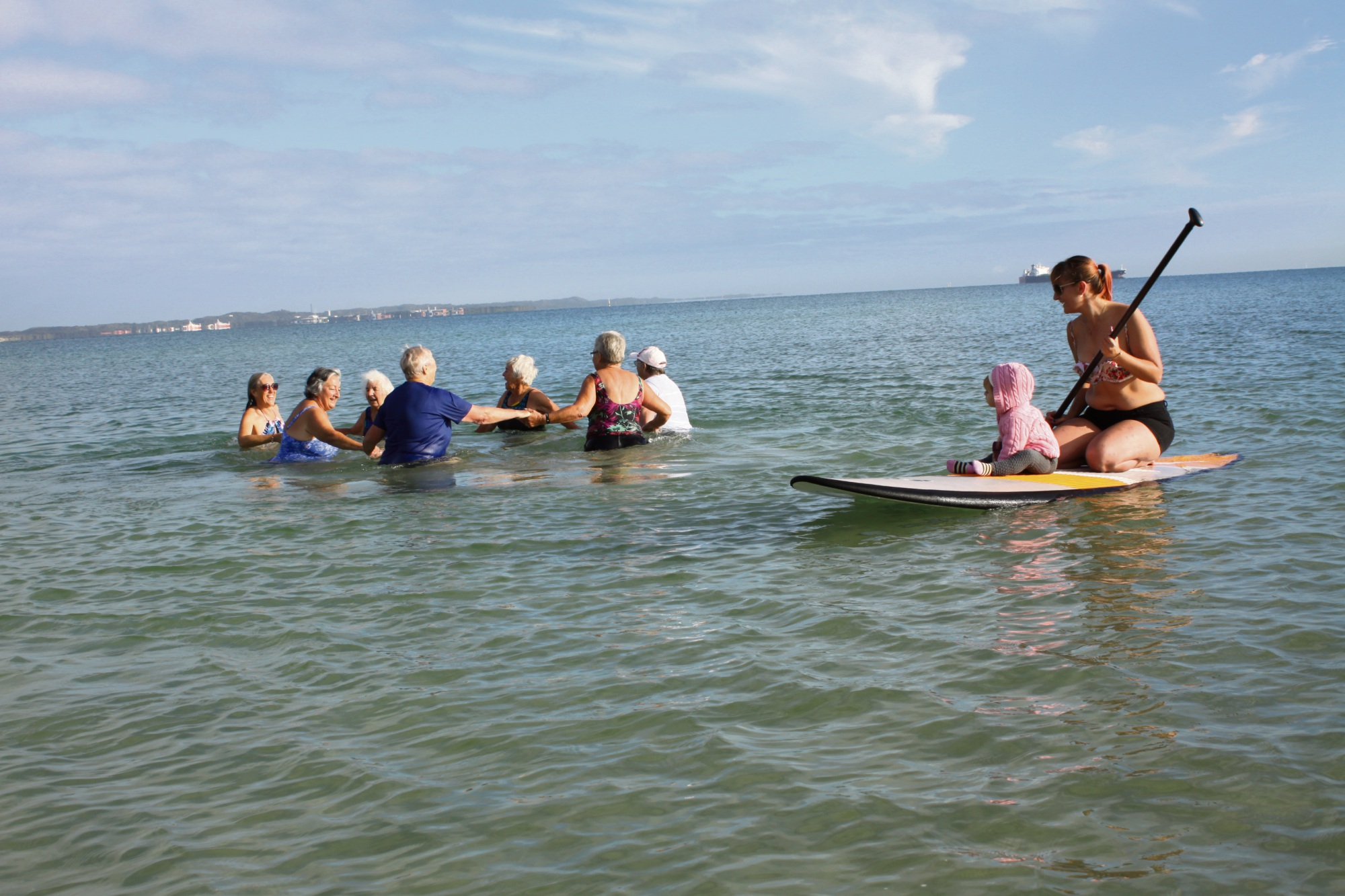 Young Luci Goodwin (on surfboard) is getting an early start on the benefits of group swimming.
