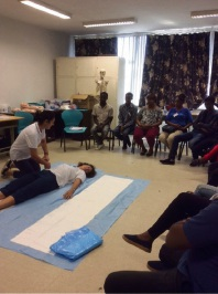 WACHS nurses Rhiann Gosper and Helen Guinness (on ground) demonstrate a log roll used to move people who have suffered trauma without causing further injury.