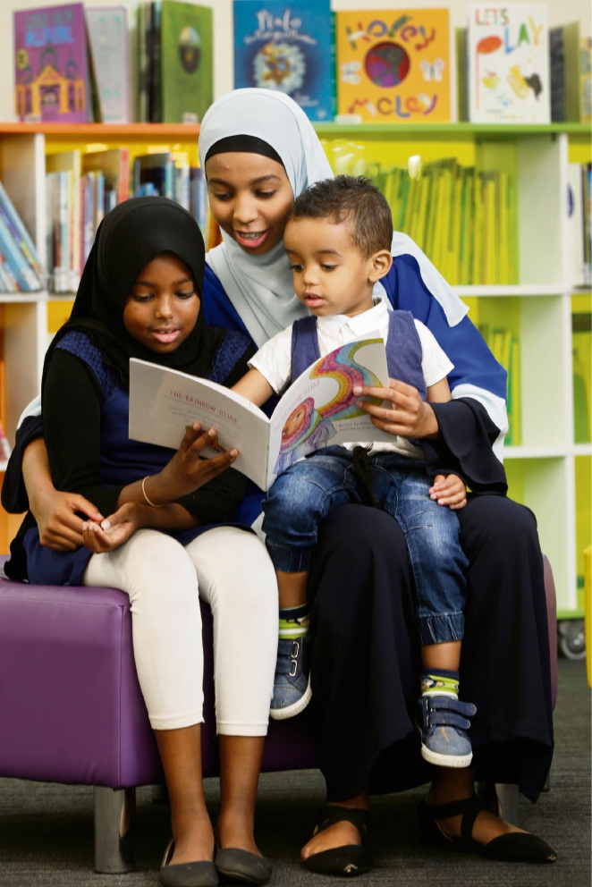 Amran Abdi reads to Maryan Abdiwohab and Layth Mukhtar. Picture: Andrew Ritchie  d467802