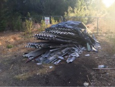 Asbestos materials dumped in front of an emergency services access way.