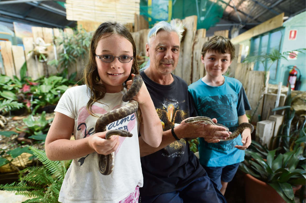 Toni Whitehead, volunteer Rich Bader and Matthew Whitehead get acquainted with Stimson pythons Rex and Monty. Picture: Jon Hewson