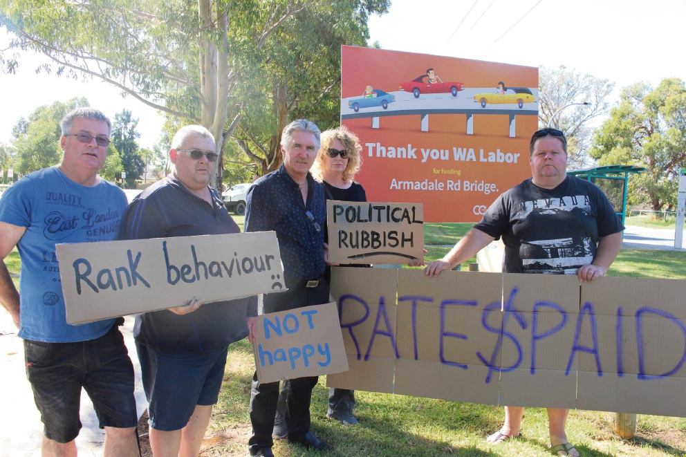 Cockburn councillor Steve Portelli with Build Roe 8 – Save Our Suburbs members Steve Greenwood, Graham Charlton, Lorna Hardy and Steve Summerell in front of a billboard in Atwell thanking WA Labor for funding the Armadale Road bridge.