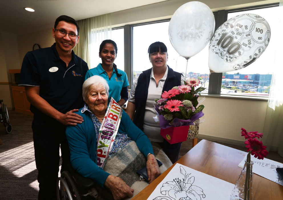 Lisa Silburn celebrates her 100th birthday with enrolled nurse JD, lifestyle co-ordinator Simi George and clinical nurse manager Melonie Miller. Picture: Matt Jelonek