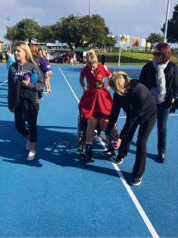 Tyla Kennedy (15) leaves the netball court in a wheelchair after a fall. On Monday she was still sore, but if the swelling has gone down enough on her knee, she may be able to play at the MNA State Championships this weekend.