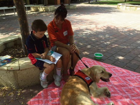 Amanda Milroy and her golden retriever Donny listen while year 2 student Kruz Sewell 7 reads.