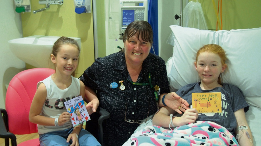 Patients Ashley Best and Katrina Giglia receiving the get well cards from the students with paediatric ward acting nurse manager Janice McEwen.