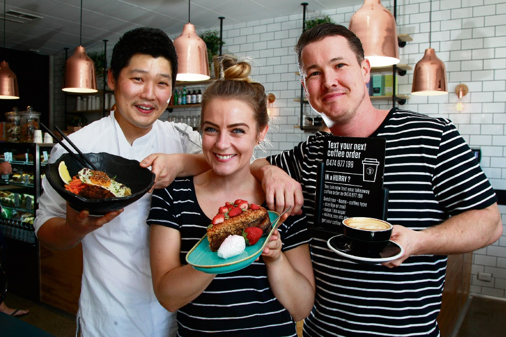Doric Street Cafe and Kitchen co-owners James Park (left) with bibimbap and Dan Murphy with staff member Meg Mousley with her lumberjack cake. Picture: Marie Nirme