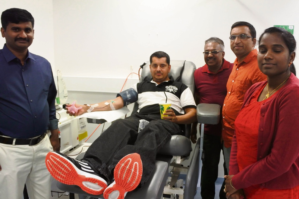 Prabhath Nair donates blood, watched by Jins James, left, and other members of the group.