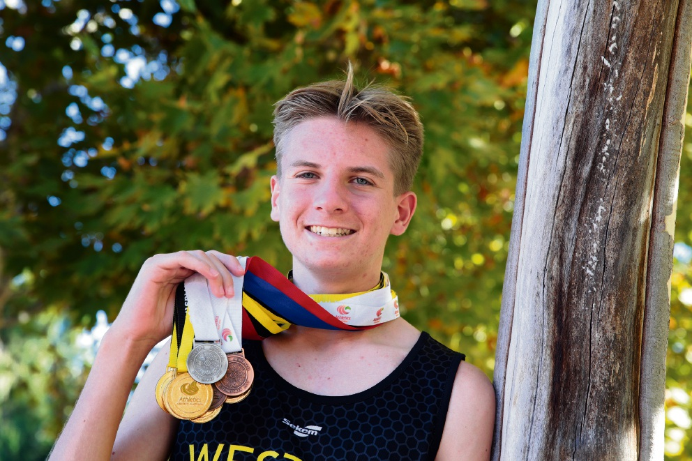 Talented athlete Dylan James proudly displays the medals he won in long jump, high jump and triple jump.